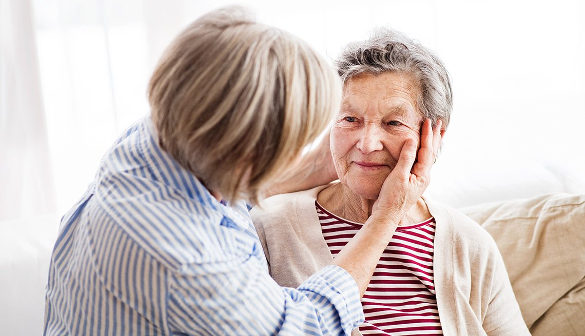 Mujer joven reconfortando a una mujer mayor
