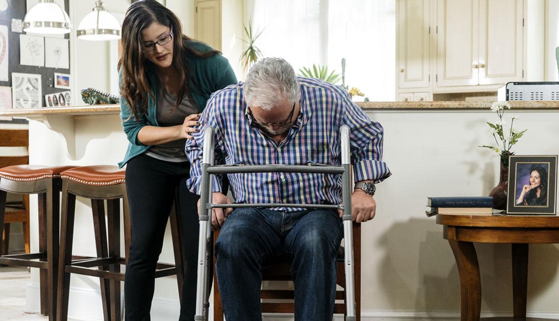 Mujer ayuda a un hombre mayor a pararse de una silla para que se sujete de un caminador.
