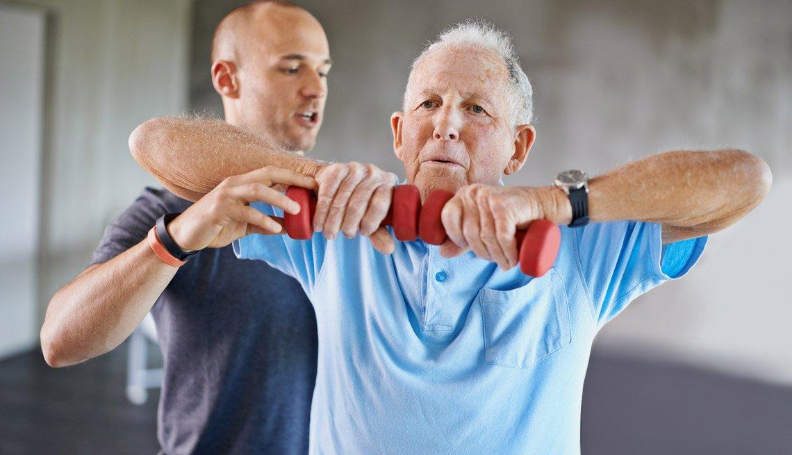 Hombre mayor levanta unas pesas guiado por un entrenador personal.