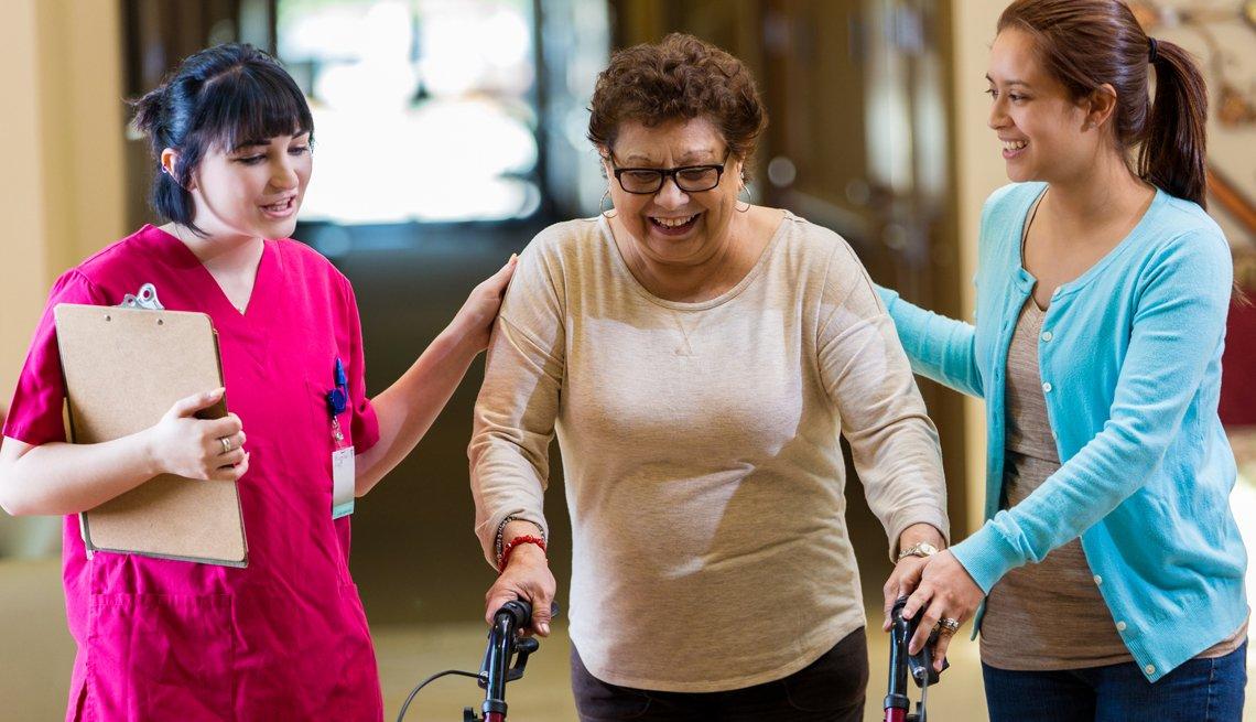 Mujer mayor hispana camina con la ayuda de un caminador y su fisioterapeuta en un hogar de ancianos. La nieta de la mujer también está presente.