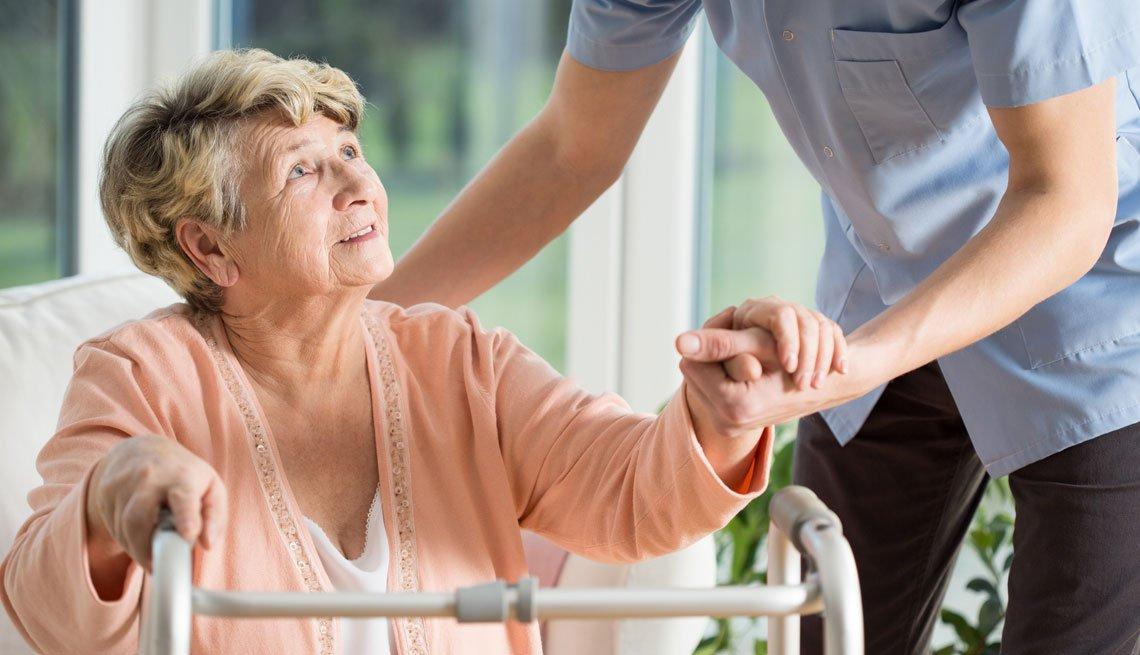 Mujer adulta mayor se apoya en un caminador mientras un hombre la ayuda a pararse.