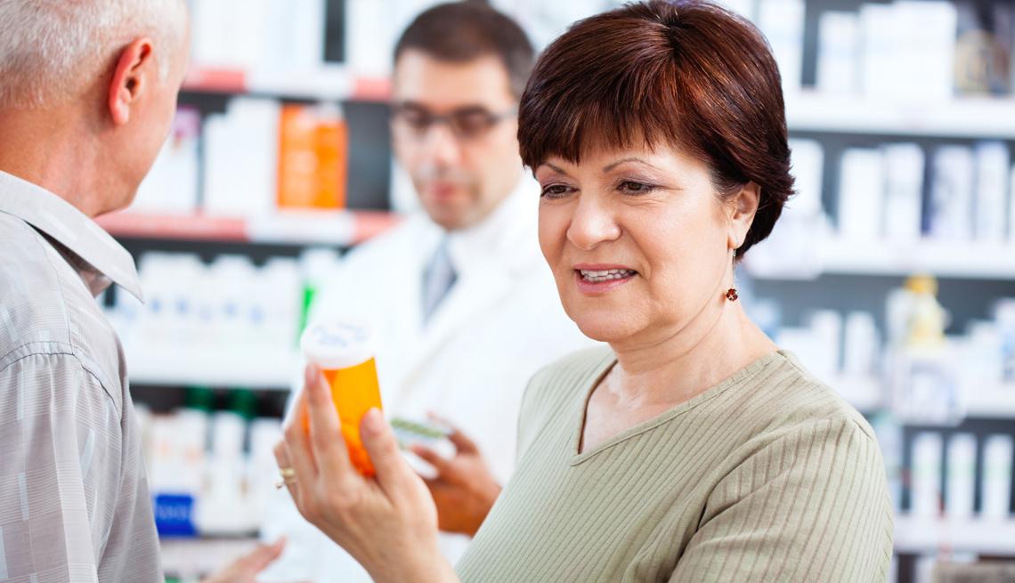 Mujer mayor sostiene un recipiente con medicamentos para el dolor en una farmacia.