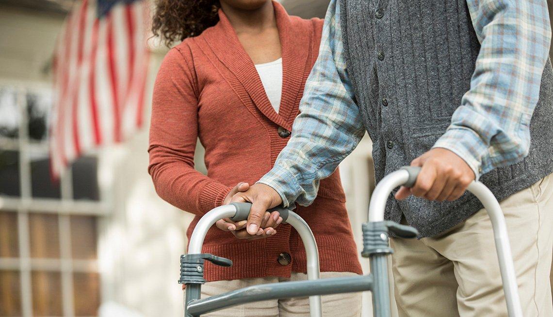 Mujer ayuda a un hombre que camina con un andador