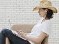 Mujer con sombrero vaquero escribiendo en un computador portátil