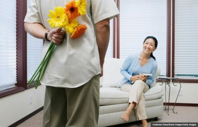 Man holding flowers behind back for his date, Dating terms in Dater's Dictionary