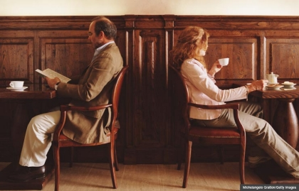 Man and woman sit back to back at a cafe.