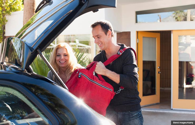 Couple loading bags into car, Overnight date (Blend Images/Alamy)