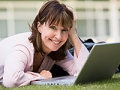 Woman using laptop outdoors. How-to guide to using AARP's dating site with How About We.