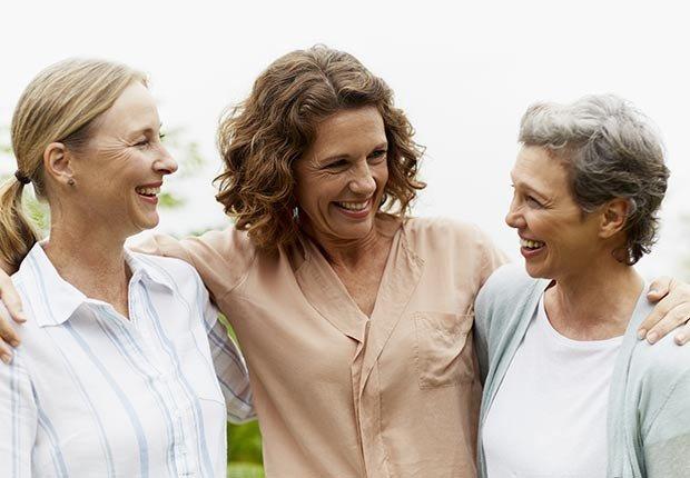 Tres mujeres sonriendo y abrazándose - ¿Por qué los hombres deberían salir con mujeres de su misma edad?