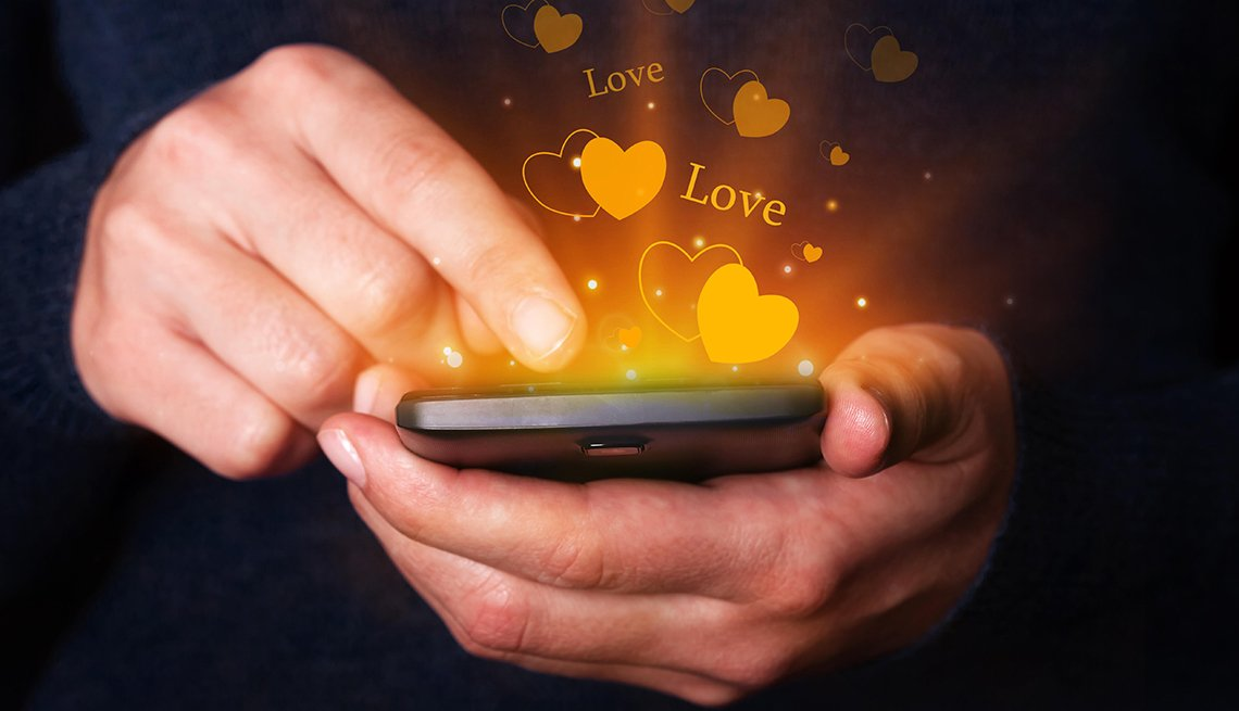 Woman hands holding and using smartphone mobile or cell phone for texting or messaging with hearts and love bubbles coming out of the phone
