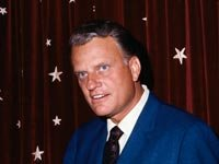 Evangelist Billy Graham in front of an American flag.