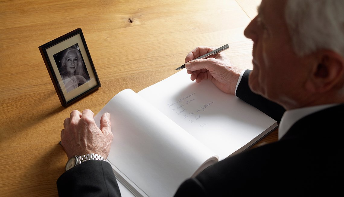 man sitting at a desk with a pen and notepad writing a eulogy while looking at a picture of his late wife