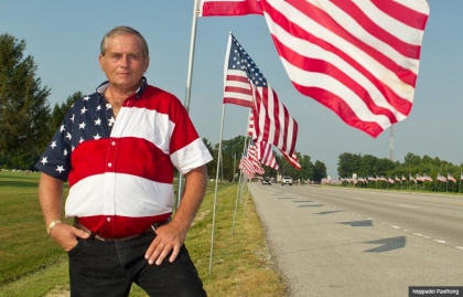 Larry Eckhardt, 54 of Little York, IL, stands next to American flags.