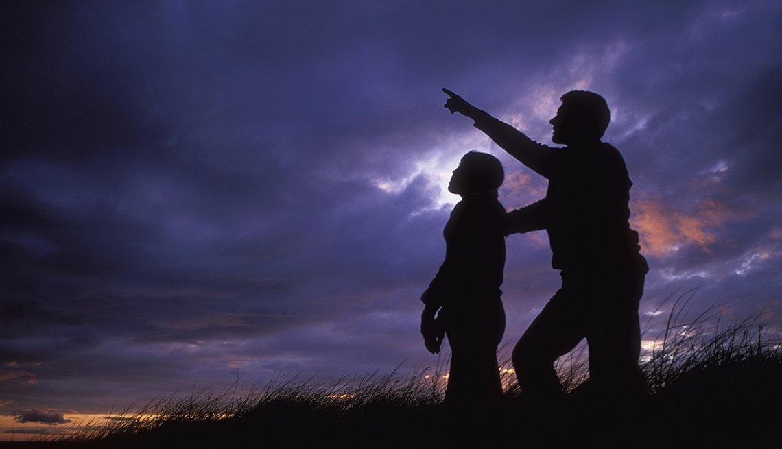 Padre e hija miran el cielo al atardecer - Diviértete con tu familia y amigos este verano