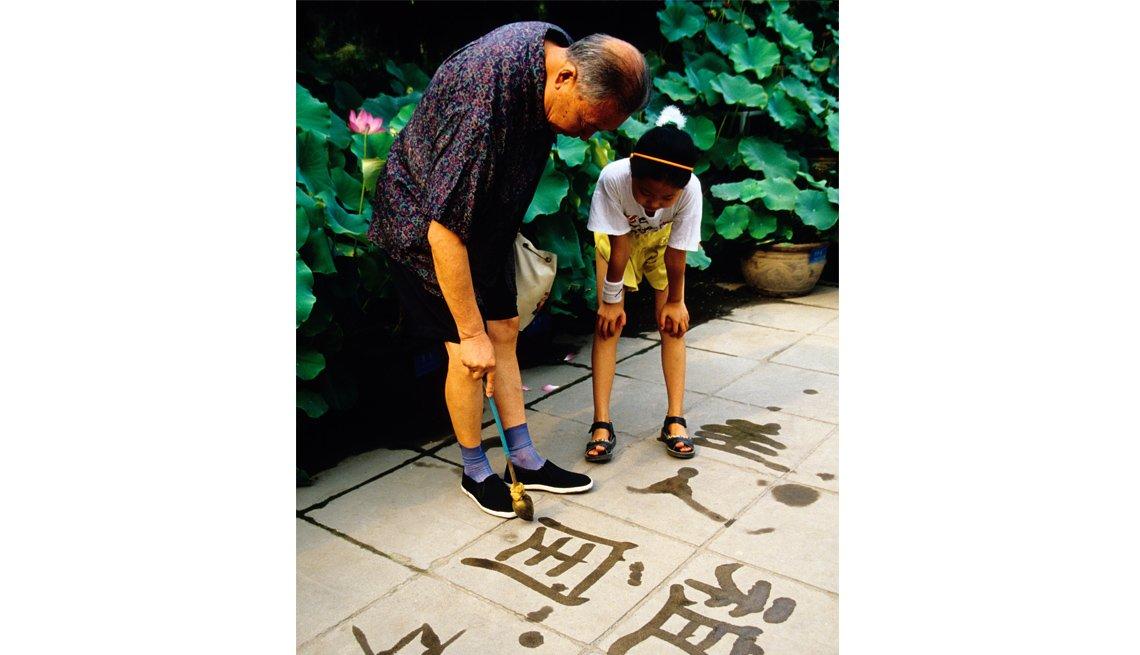 Abuelo y nieta mirando una pintura caligráfica en la acera - Diviértete con tu familia y amigos este verano