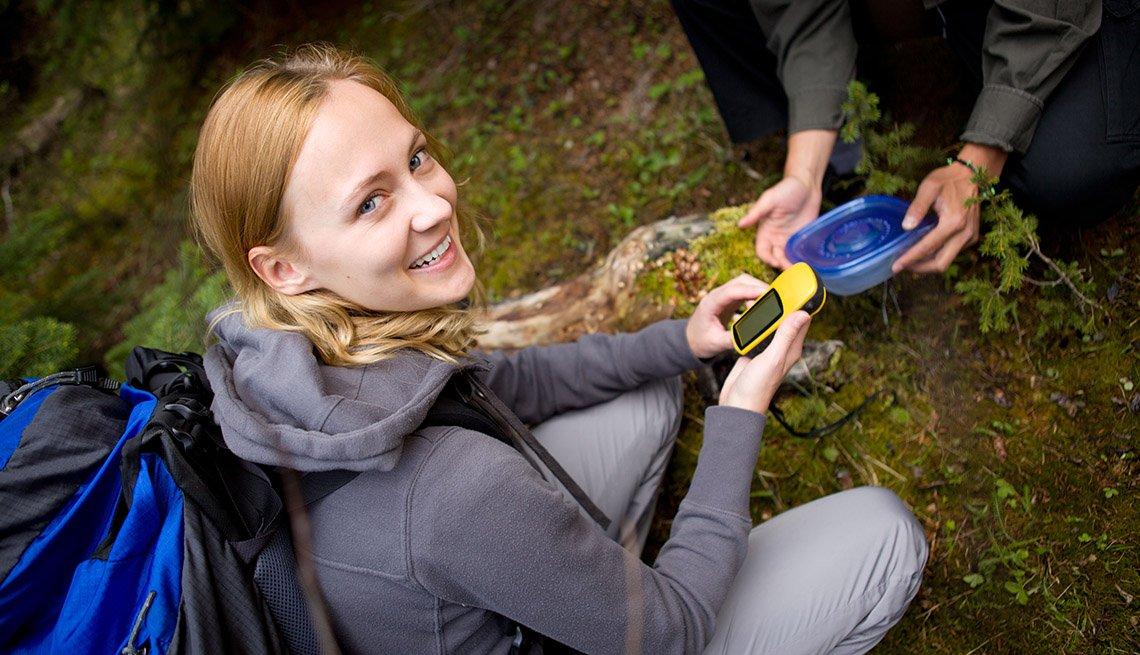 Mujer joven con un GPS en la caza del tesoro - Diviértete con tu familia y amigos este verano