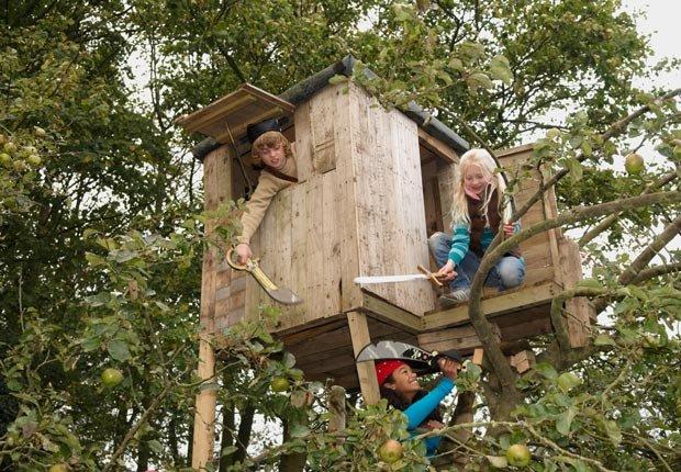 Niños juegan en una casa del árbol - Diviértase con su familia y amigos este verano