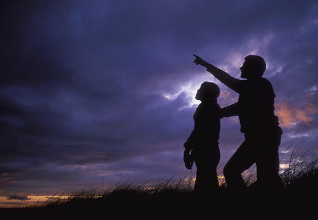 Father and daughter silhouetted against dusk sky, Stargaze, Have Fun with Your Family & Friends This Summer (blickwinkel/Alamy)