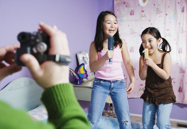 Dos niñas cantando y grabando un vídeo - Diviértase con su familia y amigos este verano