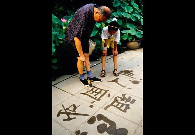 Abuelo y nieta mirando una pintura caligráfica en la acera - Diviértase con su familia y amigos este verano