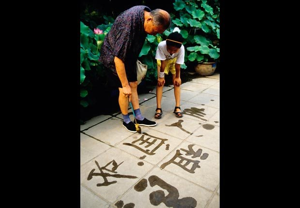 Grandfather and granddaughter paint calligraphy with water on sidewalk, Have Fun with Your Family & Friends This Summer (Dennis Cox/Alamy)