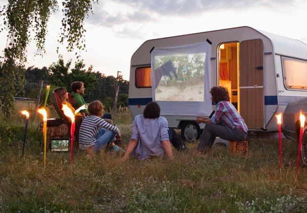 Amigos viendo proyecciones de películas al aire libre - Diviértase con su familia y amigos este verano