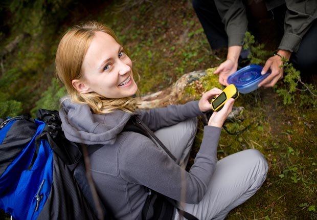 Mujer joven con un GPS en la caza del tesoro - Diviértase con su familia y amigos este verano