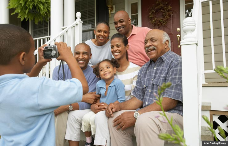 Boy takes photo of family on porch. How to create an oral family history. (Ariel Skelley/Alamy)