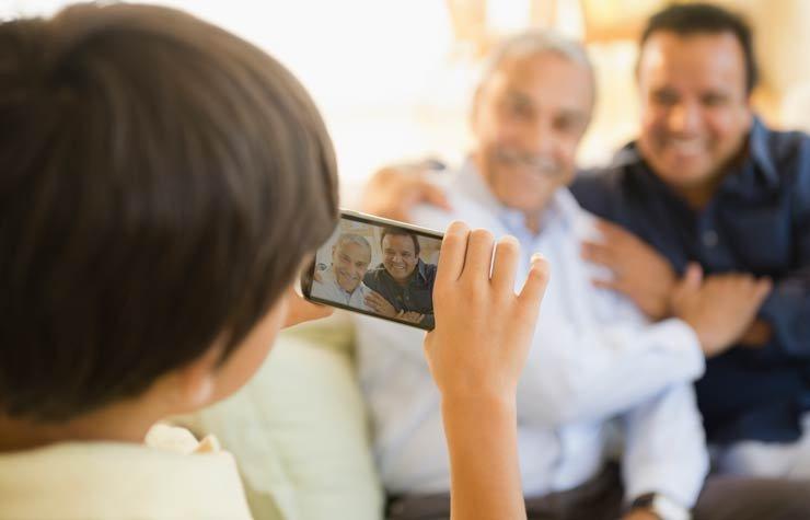 Un niño toma una foto de su padre y su abuelo. Cómo crear historias familiares orales.