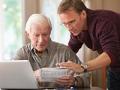 Padre e hijo que miran las finanzas. Tener la charla financiera con su familia.