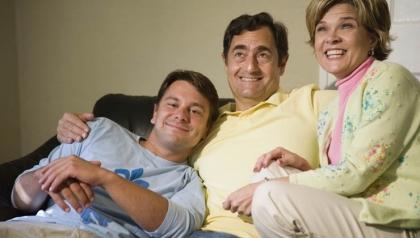 Familia sentada en un sofá y sonriendo - ayudar a las familias a apoyar a un miembro de la familia con discapacidad