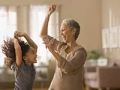 Grandmother and granddaughter dancing together.