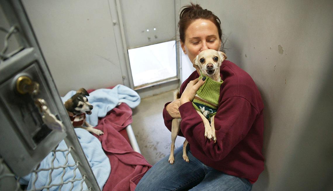 Una mujer abraza a un perro en un refugio para perros.