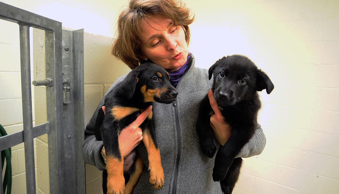 Una mujer sostiene dos perros cachorros
