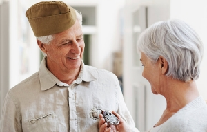Organizaciones y agencias que deben conocer todos los que cuidan - Mujer pone una medalla a un veterano de guerra