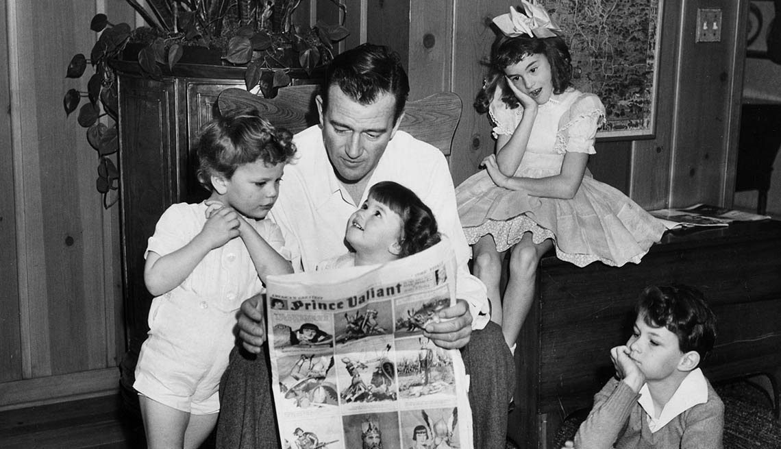 John Wayne reading to four of his children