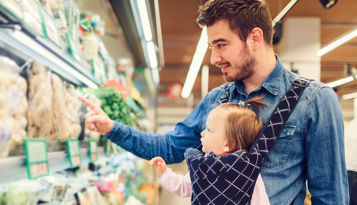 Baby wearing dad shopping at the grocery store