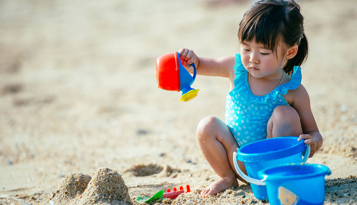 Niñita jugando en la arena - Guía para sobrevivir al verano