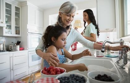Marcar la diferencia de generación en generación - Mujer mayor sonríe mientras está en la cocina con dos niñas
