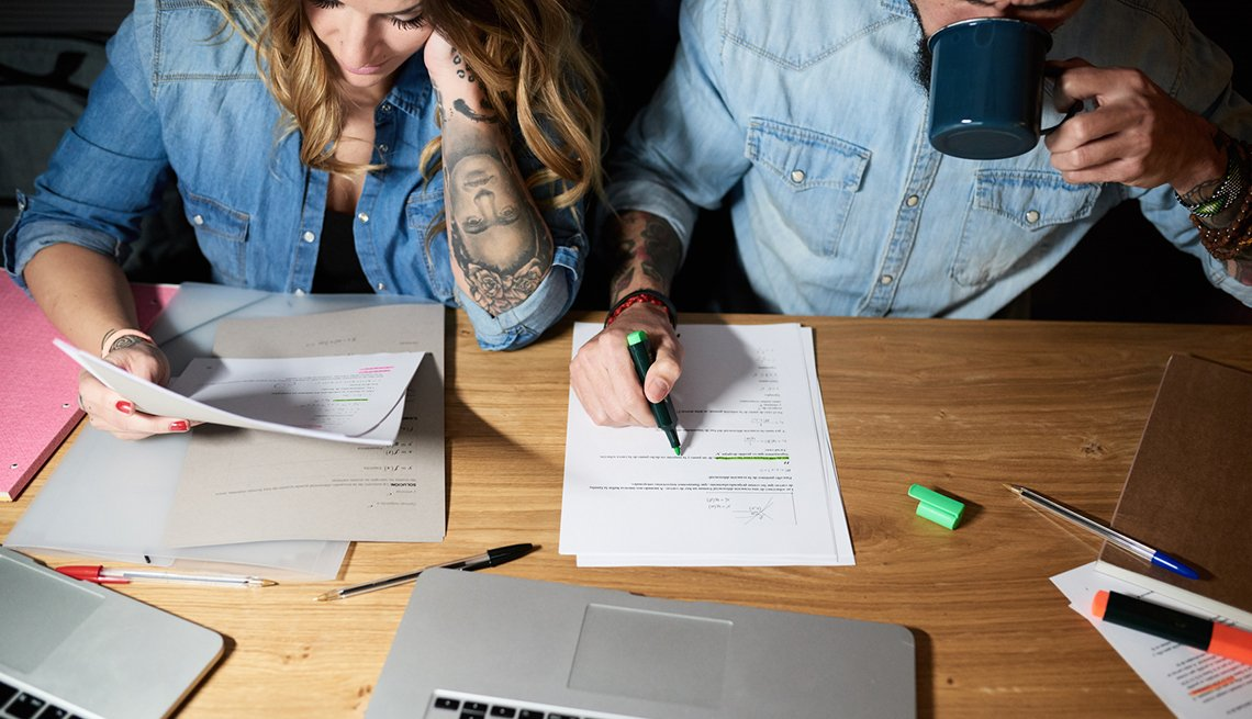 Couple in denim shirts working together at desk.