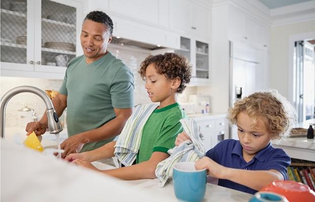 Lo que pueden hacer papás e hijos para sorprender a mamá - Papá y sus dos hijos lavan los platos en la cocina