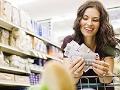 Mujer en un supermercado observando cupones para compras y aprovechando la entrada de nuevos supermercados a Estados Unidos