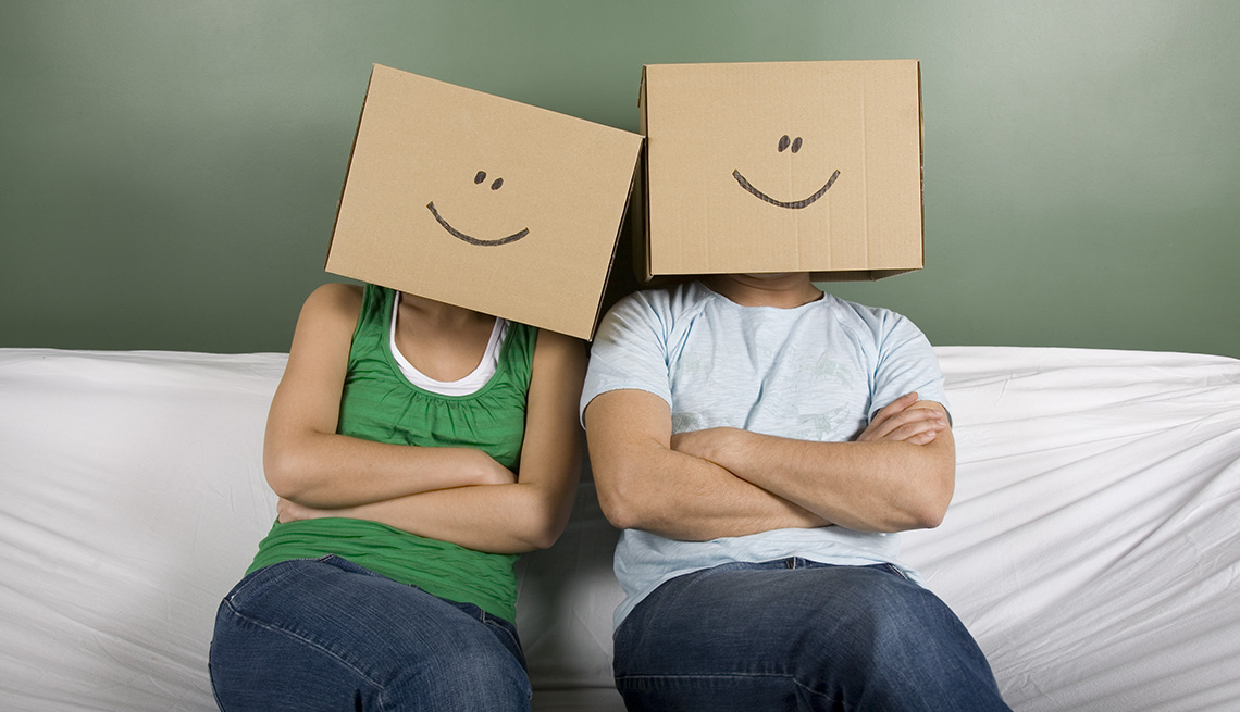 Couple Sit On Sofa Covered In White Sheet With Boxes Covering Their Faces With Smiley Faces Drawn On Them, AARP Home And Family, Can Moving Really Make You Happier?