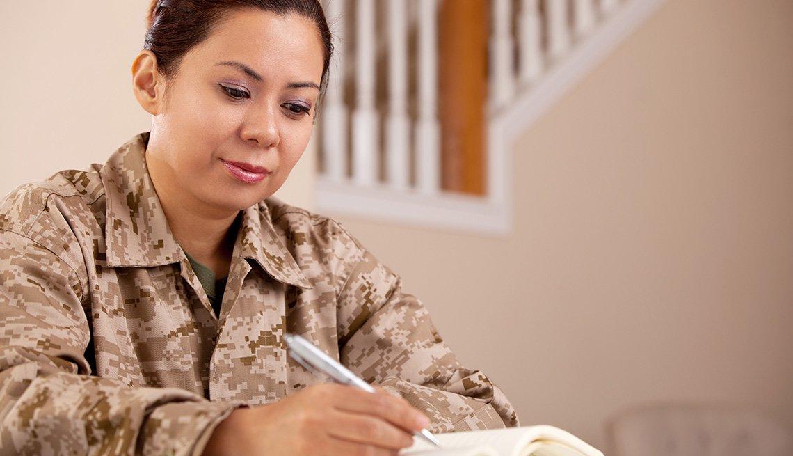 Beneficios de educación para veteranos y sus familias - Mujer sentada observa un libro