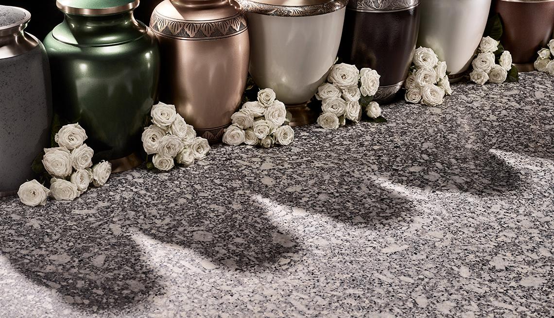 Jarrones y flores alineados en el suelo