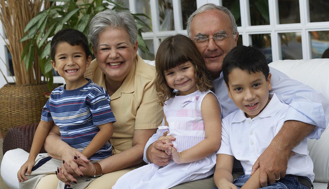 Portrato de abuelos Hispanos abrazando a sus nietos.