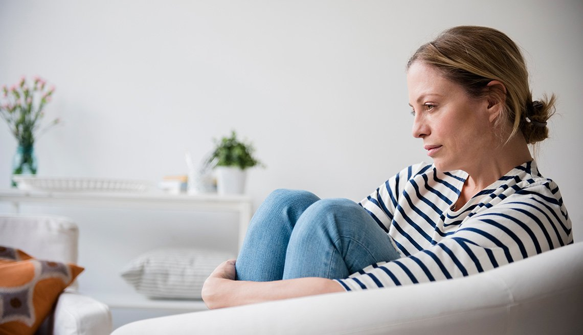 woman sitting by herself sitting on a couch