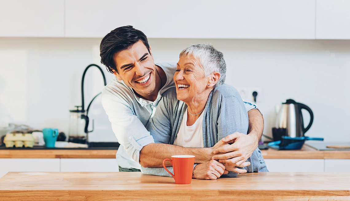 A son and senior mother laughing in kitchen