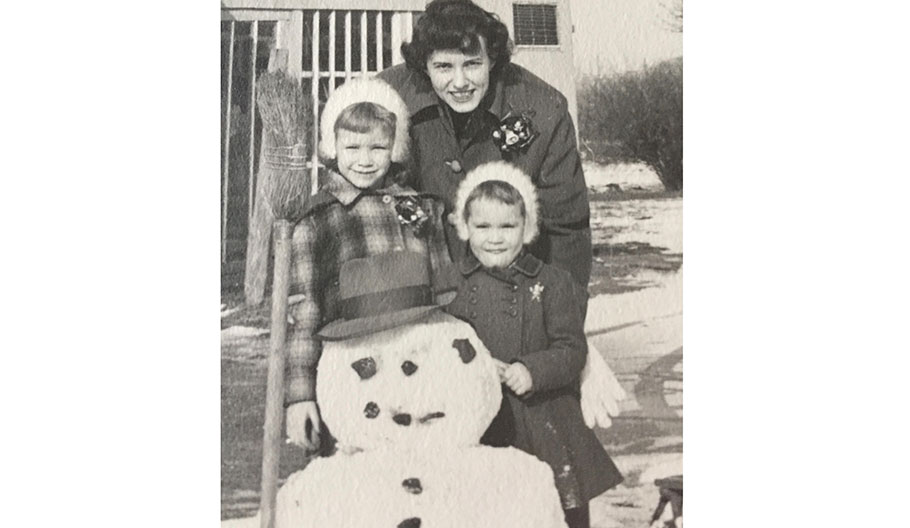 Mother with her two children posing for a photo next to a snowman