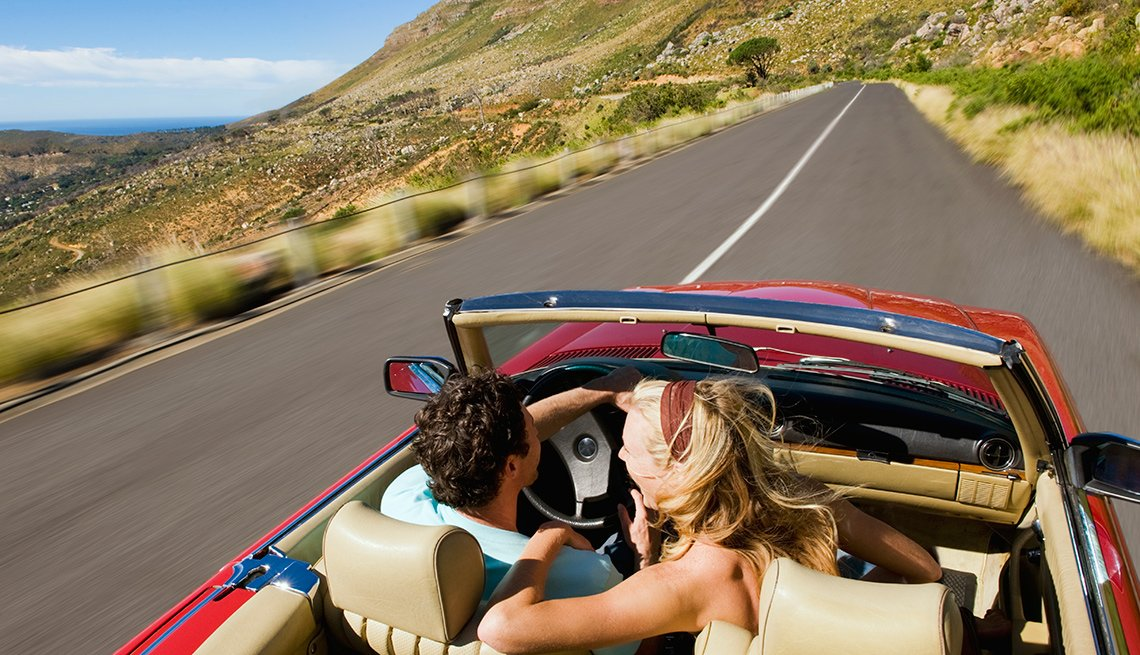 A couple in a convertible on a scenic highway